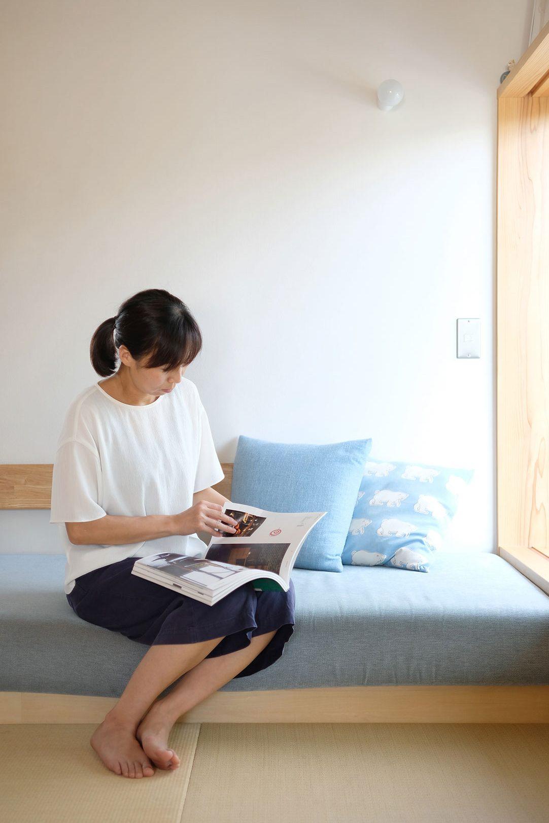 ソファーに腰掛け読み物をする